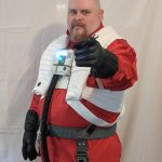 The writer dressed as a Resistance Pilot from Star Wars: The Last Jedi. Bald male, goatee, wearing a reddish jumpsuit, with a white life preserver-looking vest over it. He's pointing at the camera wearing black gloves.