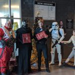 Costumed Star Wars fans standing in front of a Christmas tree